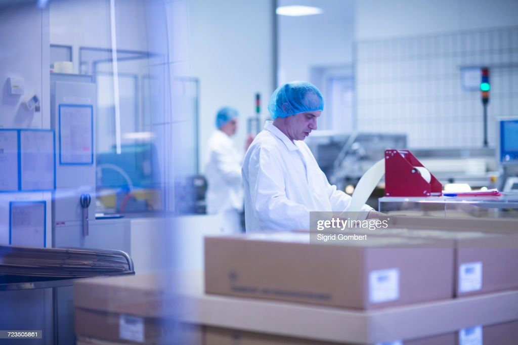 Workers packaging pharmaceutical products on production line in pharmaceutical plant : Stock-Foto