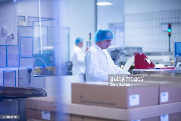 workers packaging pharmaceutical products on production line in pharmaceutical plant - sigrid gombert stock-fotos und bilder