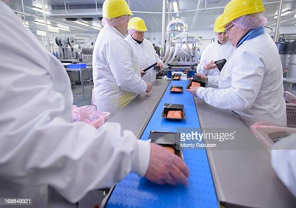 Workers packing fish fillets on production line of food factory