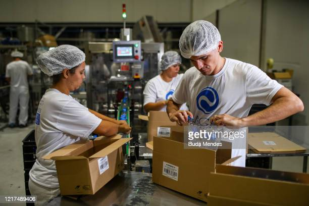 Workers packing hand sanitizer boxes on April 6 2020 in Vinhedo Brazil Ambev is producing hand sanitizers using ethanol extracted from its Barra do...