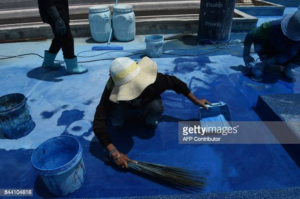 Workers paint a moat around the main funeral pyre at the cremation site for the late Thai king Bhumibol Adulyadej in Bangkok on September 8 2017...