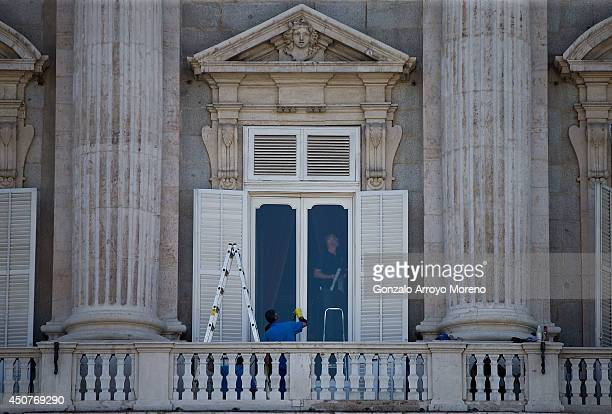 Workers paint and clean the doors of the Royal Palace balcony from where Spain's future King Felipe VI will wave to the crowds on the day of his...