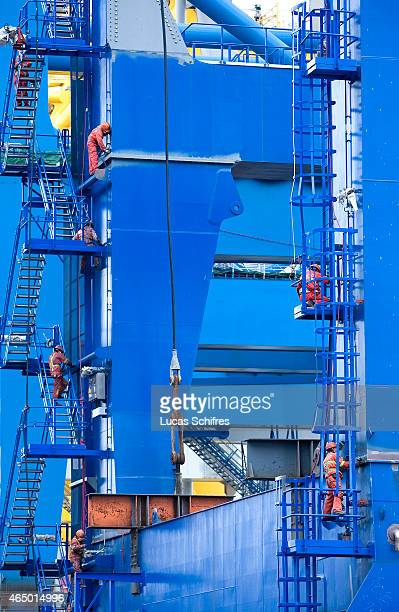 Workers paint justproduced industrial cranes outside the workshops of Shanghai Zhenhua Port Machinery Co Ltd on December 8 2009 in Changxing Island...