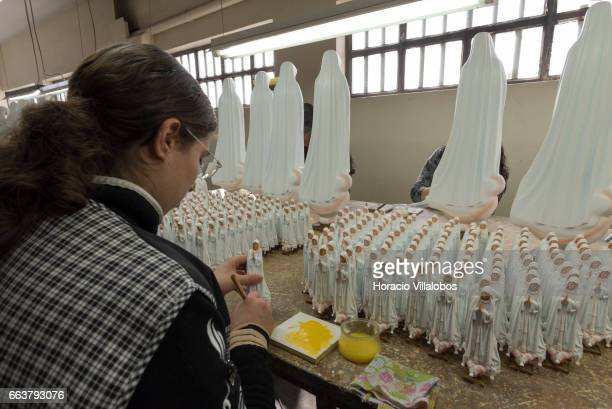 Workers paint statuettes of Virgin Mary at Farup a leading local manufacturer of religious articles on March 31 2017 in Fatima Portugal The thousands...