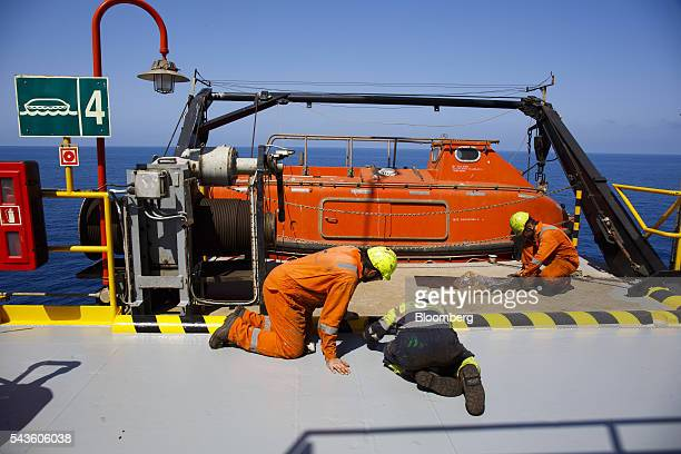 Workers paint the decking beside an emergency escape vessel on the Casablanca oil platform operated by Repsol SA in the Mediterranean Sea off the...