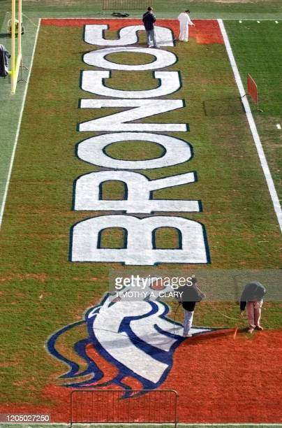 Workers paint the end zone at Mile High Stadium 16 January in preparation for the AFC Champioship game 17 January between the Denver Broncos and the...
