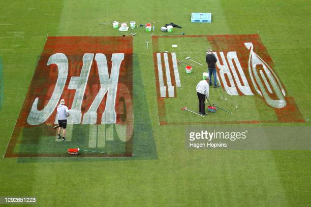 Workers paint the field with sponsor branding during a Wellington Firebirds training session at Basin Reserve on December 23, 2020 in Wellington, New...