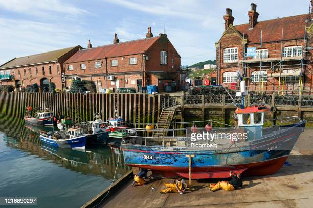 Workers paint the hull of a fishing boat in dry dock in the harbour in Scarborough UK on Tuesday June 2 2020 The threat of a nodeal Brexit is back...