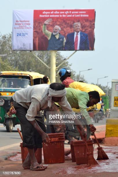 Workers paint the side of a road near Kheria Airport in Agra on february 23 ahead of US President Donald Trump first official visit to India. - US...