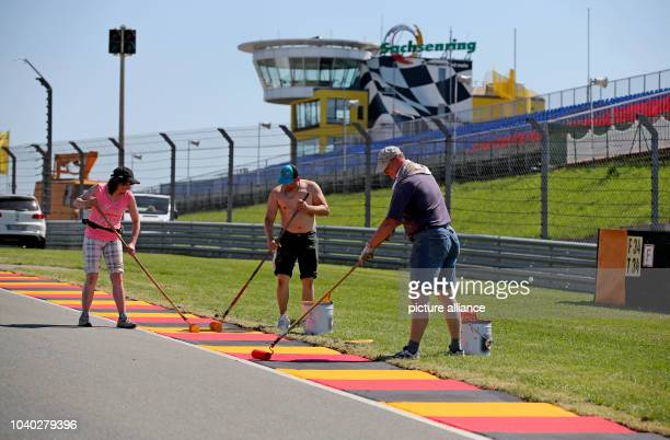 Workers paint the socalled curbs along the circuit in preparation for the German MotoGP on the 'Sachsenring' race track in HohensteinErnstthal...