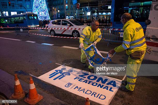 Workers painting signs for pedestrians The City of Madrid closes the traffic in main streets for Christmas to give more space to pedestrians