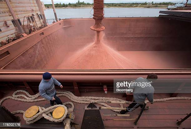 Workers pass a funnel filling the hold of a cargo vessel with potassium chloride also known as potash during shipping operations at the river port...