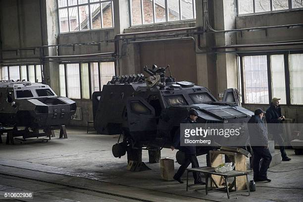 Workers pass a new DozorB armored car built for the Ukrainian army as it sits on wooden logs before having its wheels fitted in the military workshop...