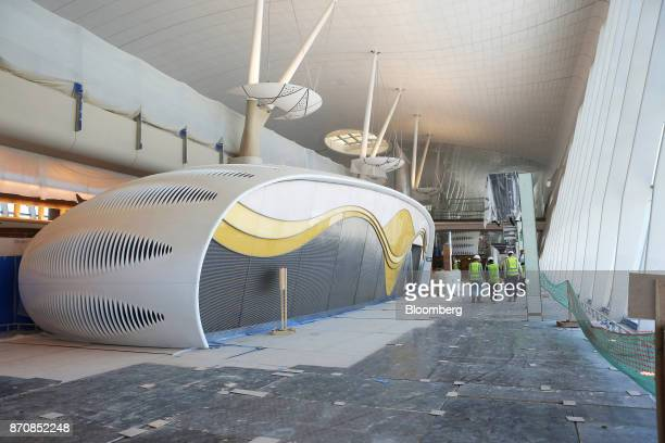 Workers pass a new toilet capsule near a boarding gate in the departures hall at Abu Dhabi airport's MidField terminal during construction in Abu...