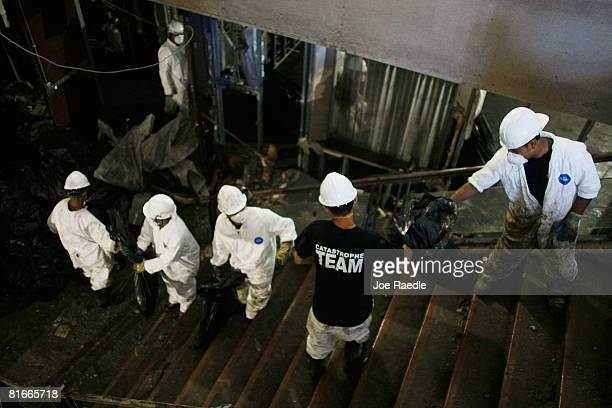 Workers pass debris up stairs as they clean out the basement of an office building after the Cedar River inundated it with flood waters June 22 2008...