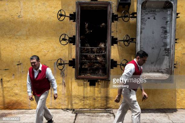 Workers pass in front of an oven loaded with agave pits referred to as pineapples at the Becle SAB Jose Cuervo distillery in the town of Tequila...