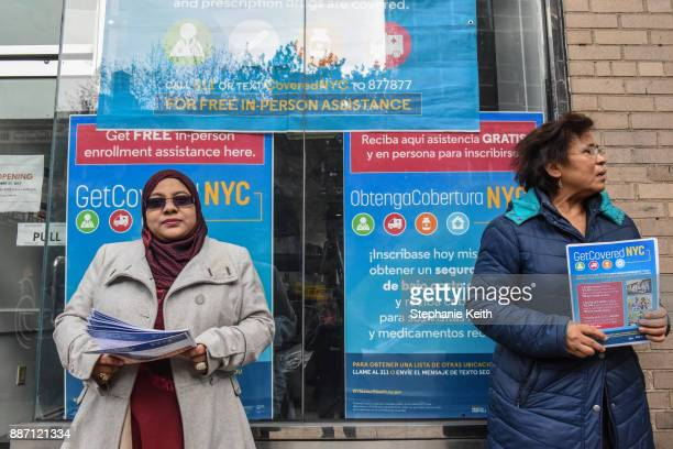 Workers pass out informational flyers in front of a new health care enrollment center on December 6, 2017 in the Queens borough of New York City....