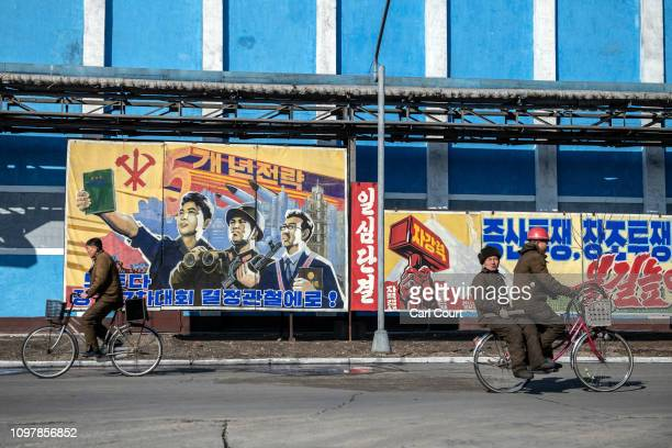 Workers pass propaganda posters as they cycle through Hungnam Fertilizer Complex on February 04 2019 in Hamhung North Korea US President Donald Trump...
