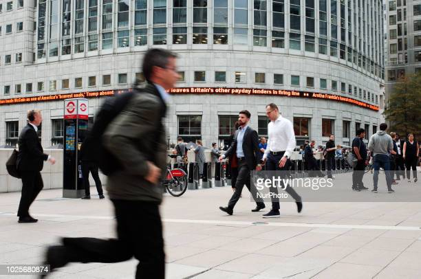 Workers pass through the central plaza of the Canary Wharf financial district on the Isle of Dogs in London England on August 31 2018 The shock...