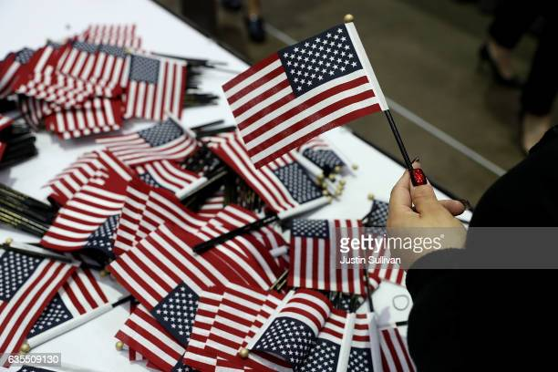 A workers passes out American flags during a naturalization ceremony held by US Citizenship and Immigration Services at the Los Angeles Convention...