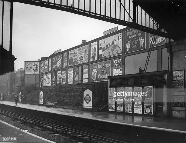 Workers paste up billboards on the walls of Walham Green Underground Station in London
