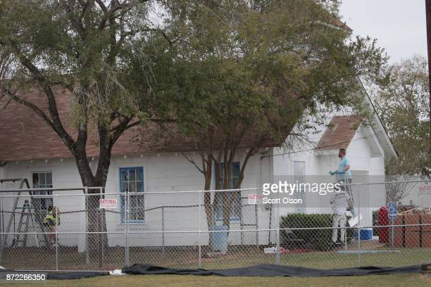 Workers patch bullet holes and paint the exterior of the First Baptist Church of Sutherland Springs on November 9 2017 in Sutherland Springs Texas...