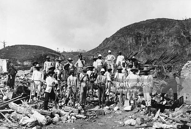 Workers pause during the futile search for survivors among the ruins of the eruption of the Mount Pelee volcano on May 10 1902 at St Pierre Martinique
