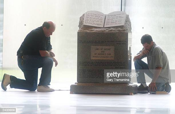 Workers pause in preparation to move the Ten Commandments monument from the rotunda of the State Judicial building August 27 2003 in Montgomery...