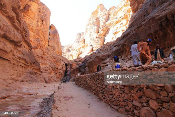 Workers pave a seating area near a manmade waterfall at Shaden a new luxury 5star desert camp under construction in Al Ula Saudi Arabia on Wednesday...