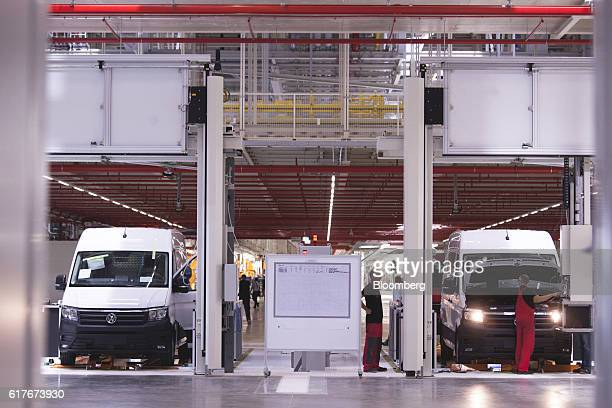 Workers perform a final quality control check at the end of the assembly line inside the newly opened Volkswagen AG manufacturing plant in Wrzesnia...