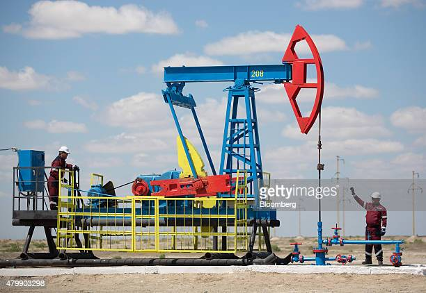 Workers perform maintenance on an oil pumping unit also known as a 'nodding donkey' at an oilfield operated by Embamunaigas a unit of KazMunaiGas...