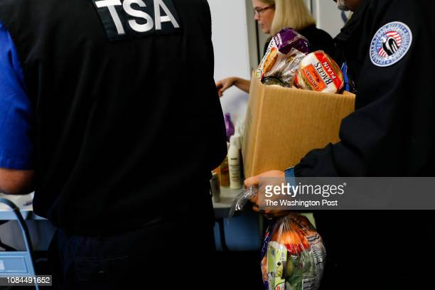 TSA workers pick up food and other items at the pop up pantry in the police training facility at the Tampa International Airport on Monday January 14...