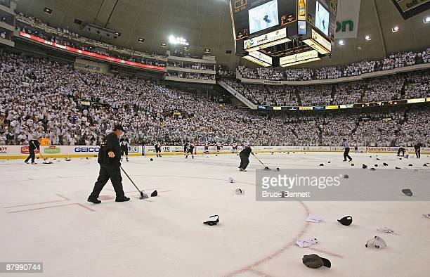 Workers pick up hats after Evgeni Malkin of the Pittsburgh Penguins scored the hat trick at 1225 of the third period against the Carolina Hurricanes...