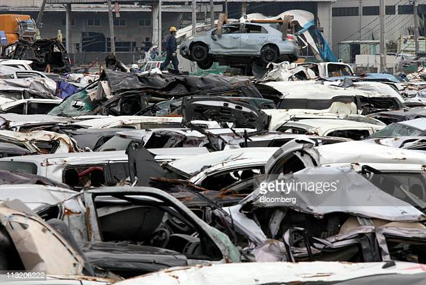 Workers pile up vehicles damaged by a tsunami following the March 11 earthquake at Sendai Port Sendai city Miyagi prefecture Japan on Wednesday April...