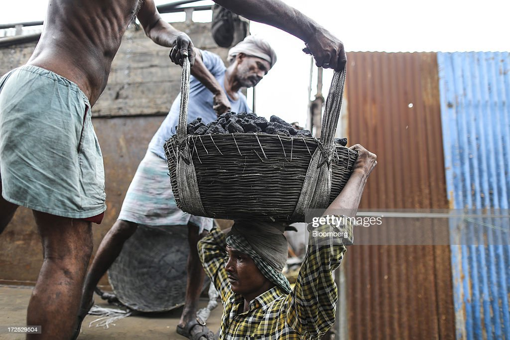 Workers place a basket of coal onto a fellow worker's head during the unloading of a truck at a coal wholesale market in Mumbai, India, on Tuesday, July 2, 2013. India, the worlds third-largest coal consumer, imported 43 percent more of the fuel than a year ago on increased demand from power stations and steelmakers, according to shipping data, and is set to eclipse China as the top importer of power station coal by 2014. Photographer: Dhiraj Singh/Bloomberg via Getty Images