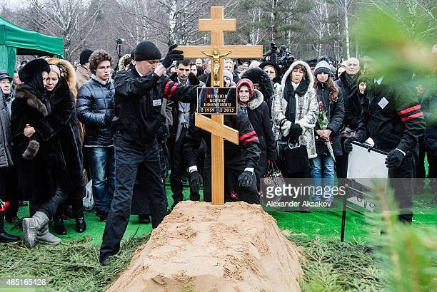 Workers place a cross to the grave of Russian opposition leader Boris Nemtsov at Troyekurovskoye Cemetary on March 3 2015 in Moscow Russia Nemtsov...