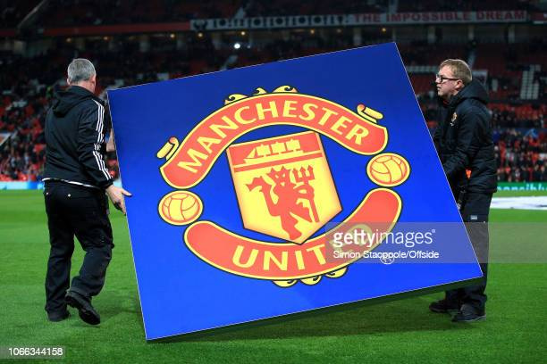 Workers place a giant Man Utd logo on the pitch ahead of the Group H match of the UEFA Champions League between Manchester United and BSC Young Boys...