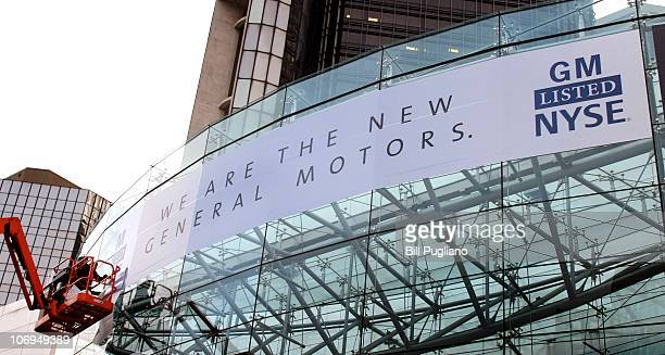 Workers place a new banner on the front of the General Motors world headquarters complex that proclaims its return to the New York Stock Exchange...