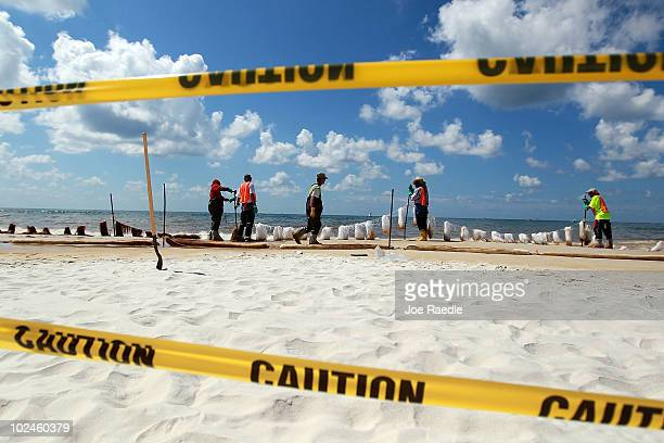 Workers place absorbent material on to the beach as oil residue washes ashore from the Deepwater Horizon oil spill in the Gulf of Mexico on June 27...