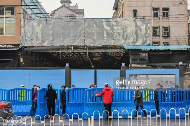 Workers place barriers outside the closed Huanan Seafood wholesale market during a visit by members of the World Health Organization team,...