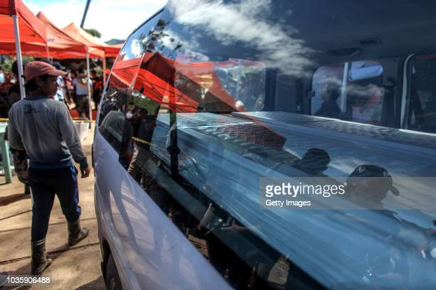 Workers place inside a vehicle a coffin of a victim killed by a landslide on September 19 2018 in Itogon Benguet province Philippines Dozens of...