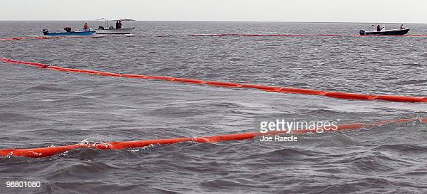 Workers place oil booms into the water in an effort to protect the coast line from the massive oil spill in the Gulf of Mexico on May 2 2010 in Drum...