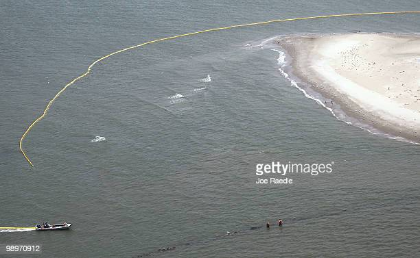 Workers place oil booms off a barrier island in the southwest region of the waters off Louisiana as they try to protect it from the massive oil spill...