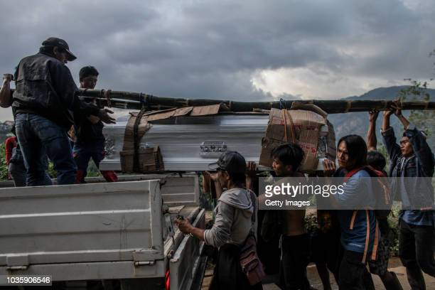 Workers place on a truck a coffin of a victim killed by a landslide on September 19 2018 in Itogon Benguet province Philippines Dozens of people are...