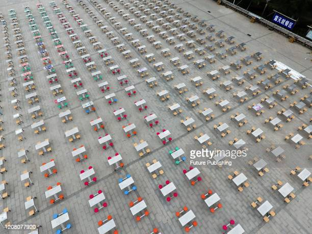 Workers place plastic-and-steel dining tables outside a canteen on a campus of a university preparing for the reopening after the long Covid-19 in...