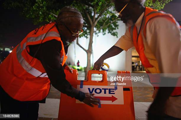 Workers place signs to guide voters to the right place on the first day of early voting in the presidential election at the Stephen P Clark...