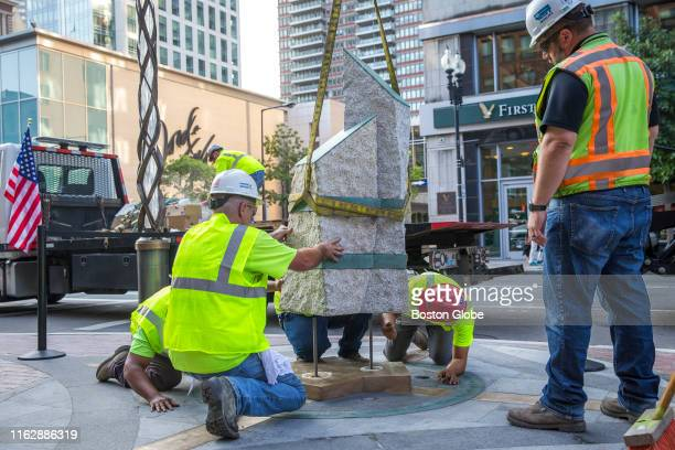 Workers place two out of the three stones commemorating the three people killed in the 2013 Boston Marathon bombings at the Boston Marathon memorial...
