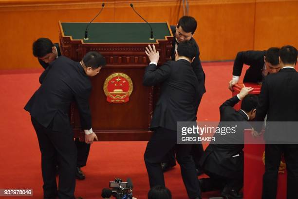 Workers position a podium for China's President Xi Jinping to use to swear an oath after being elected for a second term during the fifth plenary...
