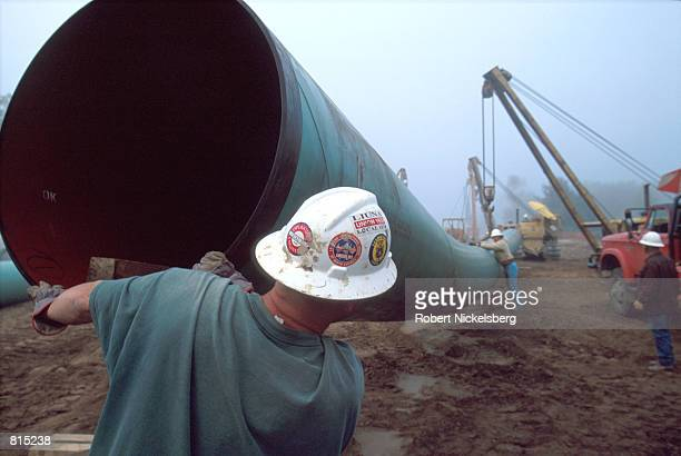 Workers position a sixton section of pipe to be laid October 3 2000 in Howell Michigan 60 miles north of Detroit The coordinates will be mapped in...