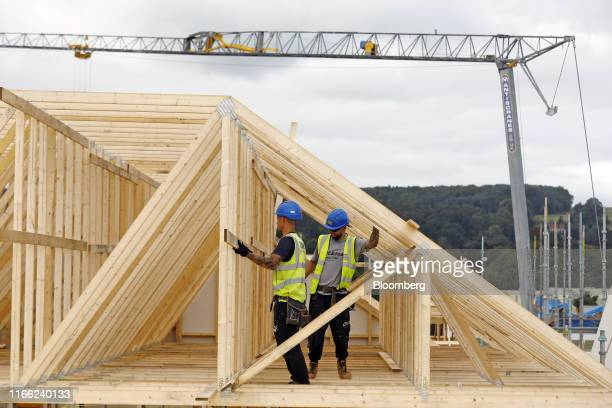 Workers position timber roof structures at a Willmott Dixon Ltd housing development construction site at Ashton Rise near Bristol UK on Tuesday Sept...